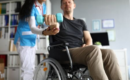 Man on wheelchair holds dumbbell in his hands. Doctor and young man in wheelchair. Treatment and restoration lost functions. Rehabilitation after injuries. Restoration motor functions hand Foto de archivo