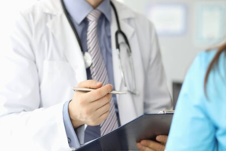 Close-up of male hand holding paper folder and writing information of patient. Professional doctor in uniform filling medical form. Healthcare and medicine concept