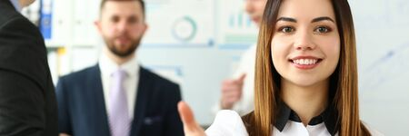 Portrait of pretty lady reaching tender arm to perform friendly gesture towards colleague or business manager. Beautiful female in classy bluse smiling at camera with joy. Company meeting concept