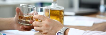 Close-up of businessmen hands clinking glasses with whiskey. Colleagues celebrating signing contract. Partners relaxing and drinking scotch after busy day. Business negotiations concept