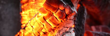 Close-up of bright flashes of fiery flames. Burning hot coals and wood in the night. Red burned by heating the particles tree. Bonfire and camping concept