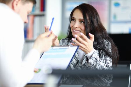 Close-up of smiling businesswoman speaking with colleague. Cute businesslady discussing financial statement with partner. Business meeting and negotiations concept