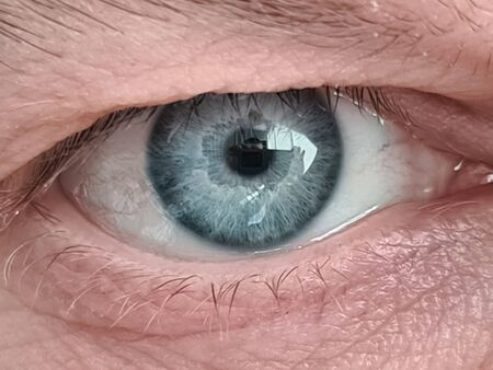 Close-up of mature mans blue eye ball. Middle-aged males face with wrinkles. Detailed picture of person. Eyebrow and eyelash. Ageing millennial skin concept