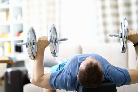 Close-up of strong fit person lifting metal heavy dumbbells at home. Cozy interior and necessary equipment to get stronger. Quarantine period. Sport and bodybuilder concept