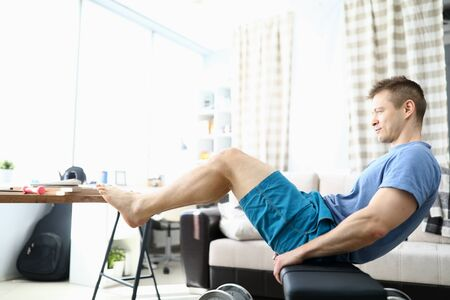 Portrait of man doing push-ups at home. Person wearing comfy sportswear and training indoors on quarantine period. Active lifestyle. Sport and healthy fit body concept