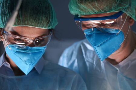 Close-up of professional surgeons woman and man in sterile medical clothes performing operation in hospital. Face masks and glasses. Modern medicine and health concept