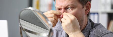 Man at home squeezes fingers acne in front mirror. Skin rashes. Person concentrates on acne during self-isolation. Improve skin condition yourself. Spending free time in apartment during quarantine