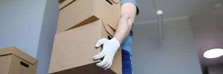 Man in work clothes and gloves carries cardboard boxes. Folding boxes. Moving waiting for loading service. Things are collected for moving. Collection goods in warehouse online store during quarantine 写真素材
