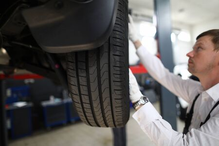 Close-up of automobile wheel tyre texture. Concentrated mechanic worker in uniform fixing car. Vehicle on repair. Service station and auto maintenance concept