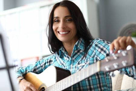 Portrait of smiling woman looking at camera with gladness. Cheerful music teacher preparing to lesson. Guitarist developing skills in playing instrument. Music hobby concept