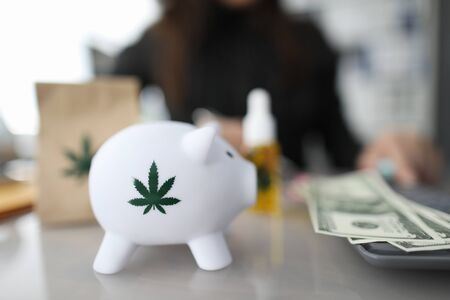 Close-up of piggy bank with green sign of cannabis. Paper package and bottle of cannabinoid oil with marijuana symbol on table. Cash on desk. Painkillers and medical marihuana concept