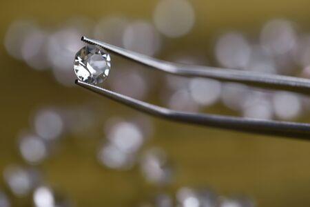 Close-up of beautiful shining crystal. Macro shot of luxury round white diamond in tweezers. Big carat size. Jeweler checking polished brilliant. Precious stone concept Stock Photo