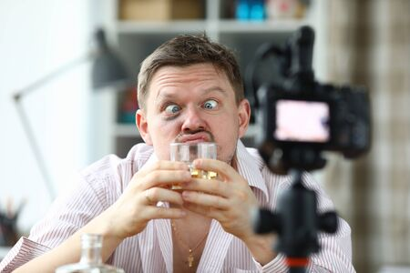 Portrait of drunk male filming on camera smelling glass of whiskey. Middle-aged man making funny face and look messy. Tasting of alcoholic drink on videocamera. Blogger concept