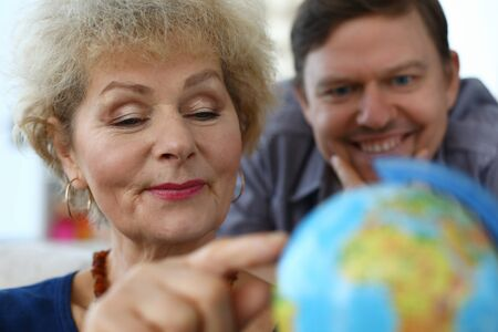 Close-up of senior woman and middle-aged man explore globe. Mother and son choose country for future travel. Modern technology and spare time together concept