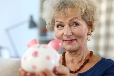 Close-up of attractive elderly woman holding piggy bank for money. Colourful container for coins and cash. Beautiful female indoors. Saving for future and economy concept