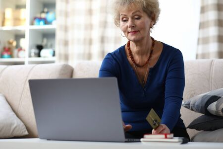 Portrait of beautiful elderly woman sitting on sofa at home. Charming female shopping via internet using laptop. Lady holding credit card. Modern technology and spare time concept 写真素材
