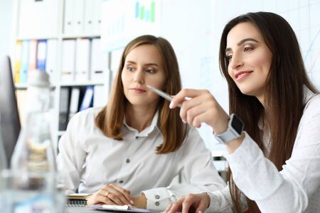 Portrait of smart businesswoman sitting at comfortable workplace and holding metallic writing pen with concentration and satisfaction. Accounting office concept 写真素材