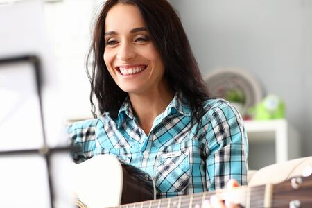 Beautiful woman plays guitar at home and laughs. Experience remote lessons during quarantine. Desire to learn and achieve best possible results in music. Noticeable growth in learning