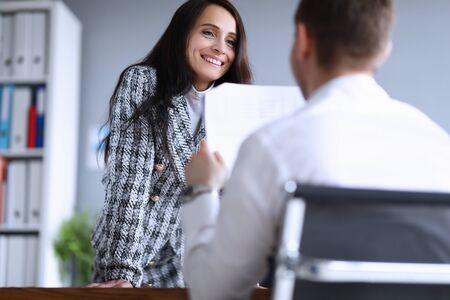 Portrait of cheerful smart businesswoman listening co-workers monthly report. Smiling female in presentable suit in company office. Finance and economy concept