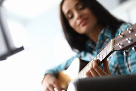 Young woman picks up guitar chords at home couch. Quality distance education during quarantine. Talent for teaching. Learning to play instrument during self-isolation. Instrumental accompaniment