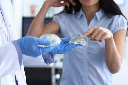 Girl in clinic touches silicone breast implant. Properly selected implants. Dense protective shell with special filler. To restore mammary glands to women after their partial or complete removal