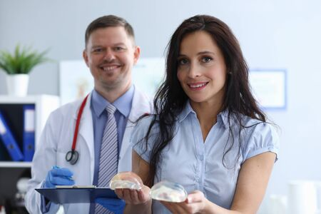 Girl in clinic holds breast implants near doctor. Comfortable atmosphere. Work plastic surgeon. Selection size breast prostheses. With men plastic surgeon at preoperative consultation