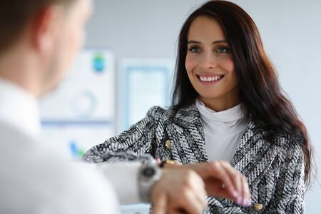 Employees man and woman compare watches and laugh. Woman seeks to use qualities employees in different ways. Ability to solve several problems simultaneously. Relations with subordinates Фото со стока