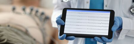 Examination and diagnosis heart, cardiogram. Doctor in white coat and silicone gloves shows tablet with an image, background is patient lying on bed. On screen device is cardiogram.