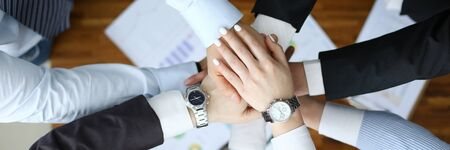Business success concept. Group people hold together hand close up top view background. Teamwork seminar education