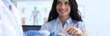 Visit to female breast plastic surgery clinic. Young women are in doctor office at plastic surgery clinic and smiling. Doctor shows patient breast implants. Consultation with an experienced surgeon.