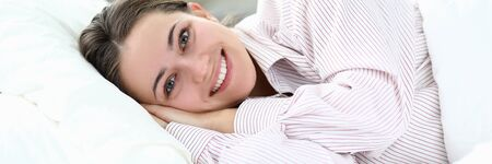 Happy girl in pajamas lies on bed and smiles. Help your body make transition to wakefulness more enjoyable. Change your lifestyle. Comfortable stay at hotel. Tune in for early awakening Stockfoto