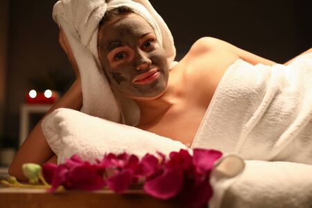 Girl with towel on her head and mud mask her face. Girl inhales pleasant scent flowers and candles. Pleasant atmosphere at home during quarantine. Facial skin will radiant, youthful and renewed Stockfoto