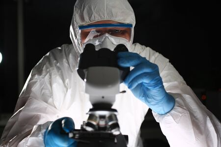 Man in protective suit looks through microscope. Research pathogenic bacteria. Special experiments and research. Healthcare in world. Virus test in laboratory