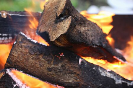 Close-up of actively smoldering embers outside. Red live coals in burning fire. Bonfire on street. Flame and sparks rise up in air. Outdoors activity and barbecue concept Banque d'images