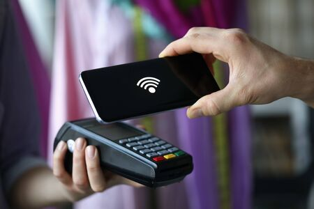 Close-up of terminal and cashless pay. Smartphone with sign on screen. Cashier machine to withdrawals money. Nfc technology counter. Finance and purchase. Contactless payment concept Imagens - 147829704