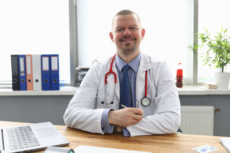 Portrait of smiling cheerful medical worker posing in office. Qualified male wearing uniform and red stethoscope. Laptop on wooden table. Medicine and healthcare concept