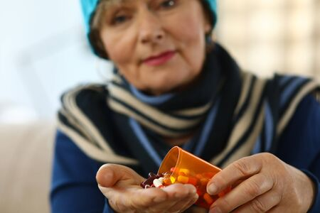Cold elderly woman falls asleep on palm capsule. Cold medicine for elderly. Weak immune system in old age. Undesirable effects drugs. Danger to elderly. Drugs for depression and anxiety