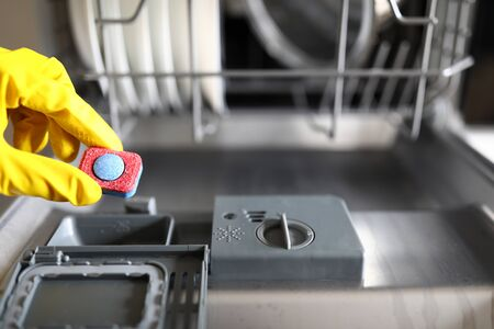 Gloved hands holding dishwasher washing tablet. Setting required washing mode. Products contain minimum foaming components. Concentrated detergent. Effective drying. We clean all surfaces dishes Archivio Fotografico