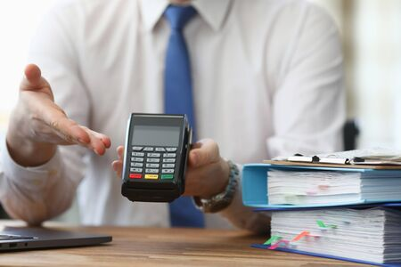Close-up of business male holding cashier electrical machine for fast payment. Nfc technology counter. Man in suit with folder on table. Transaction and pay bill on terminal
