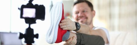 Man raised his leg and shows sneaker to camera. Video product review affects potential buyer. Description appearance sneakers. Video why this product is better than differs from others product market