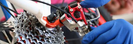 Professional adjustment in service center bike. An experienced specialist is able to service bike. Make bicycle maintenance. Highly skilled master cycling enthusiast. Diagnostics and assembly Фото со стока