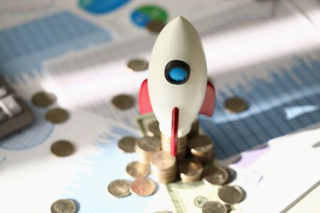 Close-up of space rocket launch as symbol for new business idea creativity success and achievement. Bunch of cash coins on table. Career growth and start up concept