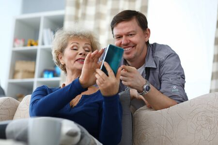 Portrait of cheerful son and mother watching old photos on smartphone. Smiling elderly woman and middle-aged man spending time at home. Precious memory ad leisure concept