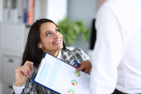 Portrait of smiling young cheerful woman get papers for sign. Happy lady in luxury costume. Clipboard with important documents. Business company and working moment concept