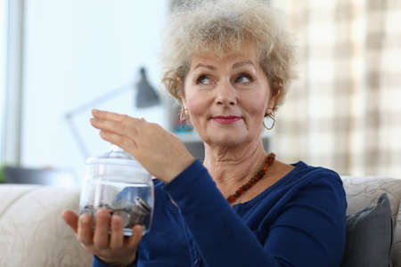 Portrait of senior charming woman holding glass container for money. Elderly female and piggy bank for coins and cash. Smiling lady indoors. Savings and finance concept Stock fotó