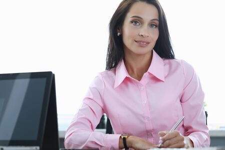 Portrait of smiling beautiful brunette office worker sitting in presentable suit. Pretty manager holding silver pen. Stylish pink blouse. Business and employee concept