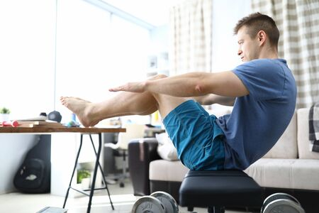 Close-up of man doing push-ups at home. Male wearing comfy sportswear and training indoors on quarantine period. Healthy strong and fit body. Sport and active lifestyle concept 版權商用圖片