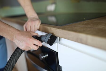 Close-up of man from professional cleaning service clean kitchen furniture with vacuum cleaner. Handyman prepare room after renovation. Cleanliness and household concept