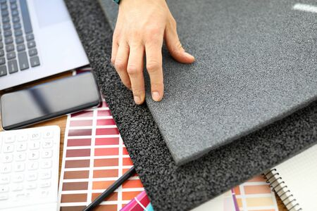 Top view of persons hand and colourful palette samples on working table. Grey material for apartment renovation. Modern laptop on desk. Creative designer and architect concept 스톡 콘텐츠