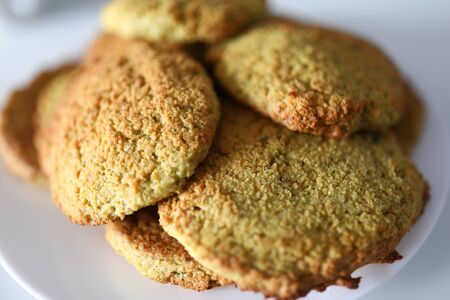 Close-up of oatmeal cookies on white plate. Macro shot of delicious homemade biscuits. Sweets and dessert for tea or coffee. Bakery and confectionery concept